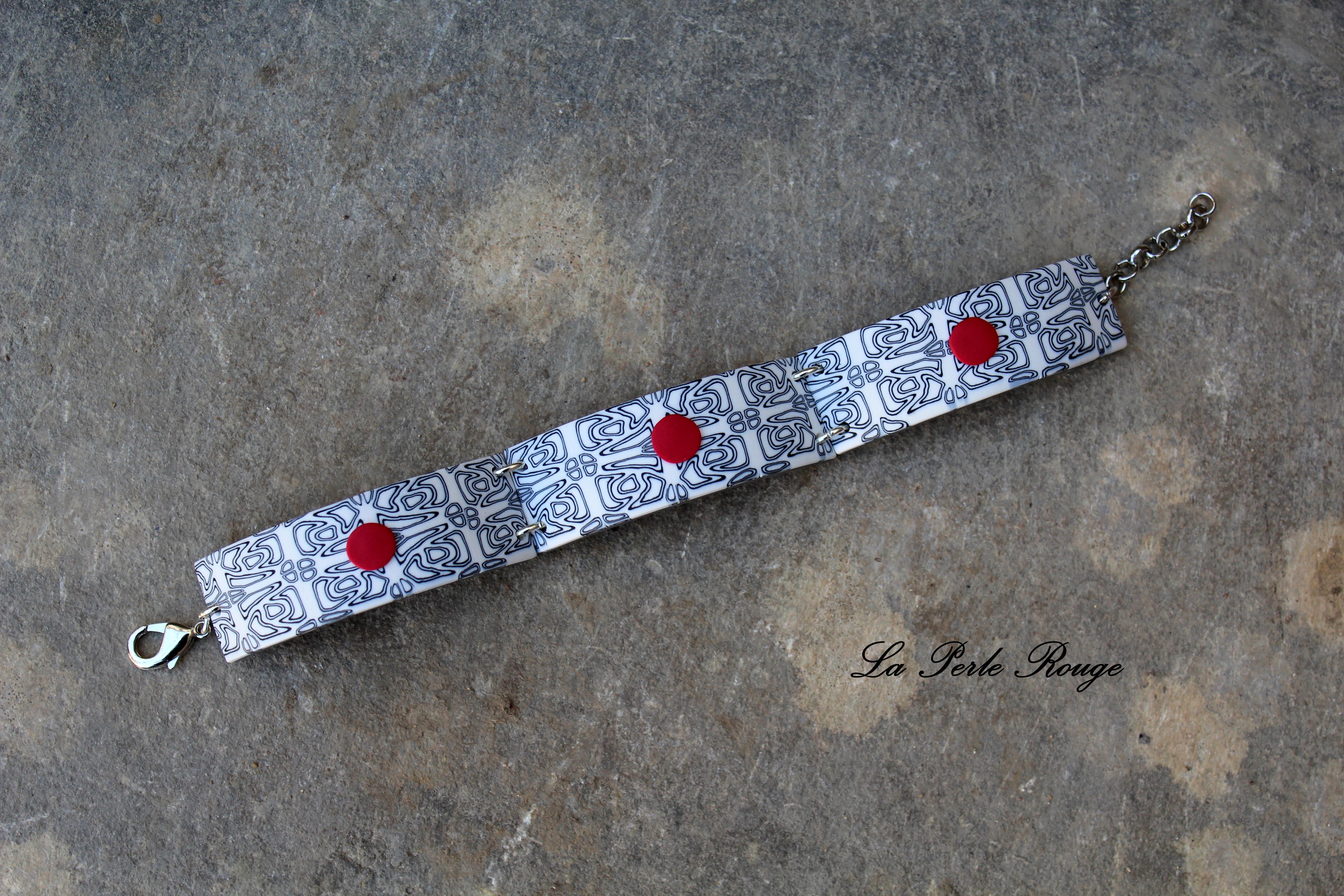 Bracelet noir et blanc et ses pitites pastilles rouges.